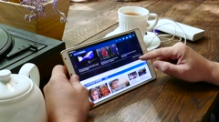 Man visits euronews web site on tablet pc in a cafe Stock Footage