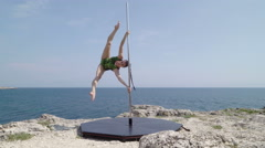 Fit girl performs pole dance acrobatic tricks during extreme fitness workout Stock Footage