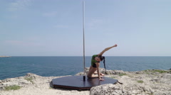 Fit girl during extreme outdoor pole dance workout on a cliff above blue sea Stock Footage