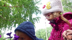 Blond boy and girl with glasses sniffing flowers. Children have fun and laugh Stock Footage