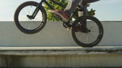 SLOW MOTION CLOSE UP: Young bmx biker jumping ollie and wiring wheelie trick Stock Footage