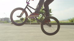 SLOW MOTION CLOSE UP: Extreme bmx biker riding wheelie and jumping ollie in park Stock Footage