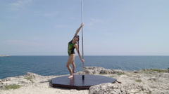 Extreme pole dancing fitness exercise on the edge of rock Stock Footage