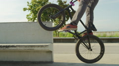 SLOW MOTION CLOSE UP: Young extreme bmx biker jumping ollie and riding on a ramp Stock Footage