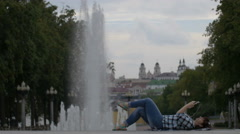 Woman lies near the fountain in the city listening to music, and uses the phone Stock Footage