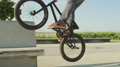 SLOW MOTION CLOSE UP: Extreme bmx biker jumping on bench and doing wheelie trick Stock Footage