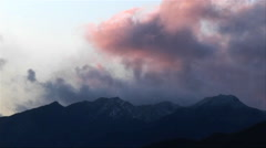 Dark clouds roll in over low mountains near sunset. Stock Footage