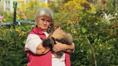 Portrait of an elderly woman with a cat in the garden Stock Footage