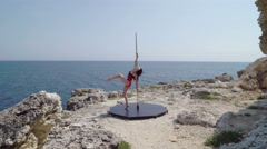 Pretty woman performing pole dance on rocky cliff by sea Stock Footage