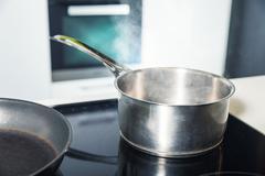 Pan and pot on the stove Stock Photos