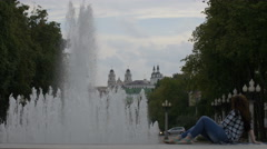 Woman relaxing near the fountain in the city listening to music Stock Footage