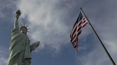 A time lapse of clouds moving over the Statue of Liberty and an American flag. Stock Footage