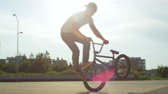 SLOW MOTION: Extreme bmx biker doing cool tail whip tricks on city street Stock Footage