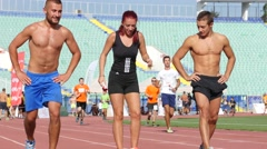 Young healthy strong body sport people warm-up muscles befor running relay race Stock Footage