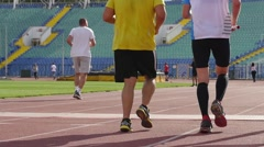 Strong healthy body legs people run on running stadium tracks during relay race Stock Footage