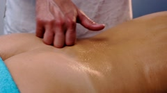 Male hands pouring oil and massaging patient's back Stock Footage