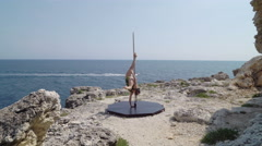Strong woman dancing on portable dance and fitness pole above the sea Stock Footage