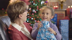 Little girl holding her Christmas present on grandmother's lap Stock Footage