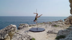 Upside down pole dance tricks on a rock above the sea Stock Footage
