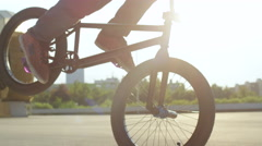 SLOW MOTION EXTREME CLOSE UP: Bmx rider doing cool tricks and riding reverse Stock Footage