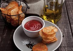 Potato crisps with ketchup on plate and olive oil. Wooden background Stock Photos