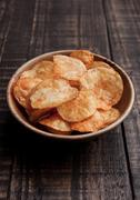Bowl with potato crisps chips on wooden board. Junk food Stock Photos