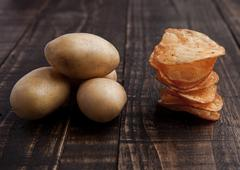 Fresh potatoes and crisps healthy and junk food on wooden board Stock Photos
