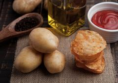 Fresh potatoes and crisps with pepper and sause on wooden board.Potatoes,ketc Stock Photos