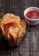 Bowl with potato crisps chips and ketchup on wooden board. Junk food Stock Photos