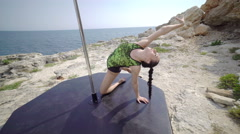 Pole dance sport exercise with portable stage pole on rocky cliff 4k Stock Footage