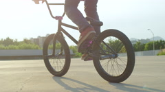 SLOW MOTION EXTREME CLOSE UP: Bmx rider doing cool tricks over the sun at sunset Stock Footage