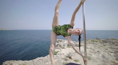 Pole dancer using portable pole fitness stage on rocky cliff. Steadicam shot 4k Stock Footage