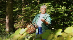 An elderly woman shows a coral mushroom in the forest Stock Footage