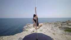 Young woman using portable dance and fitness pole on a cliff. Steadicam shot 4k Stock Footage