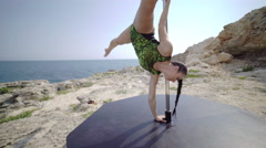 Extreme fitness pole dance workout on a cliff above the sea. Steadicam shot 4k Stock Footage