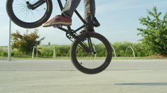 SLOW MOTION CLOSE UP: Unrecognizable man riding bmx bike and jumping bunny hop Stock Footage