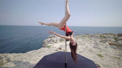 Pole dance sport exercise on rocky cliff. Steadicam shot 4k Stock Footage