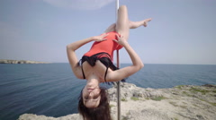 Pole dancing fitness exercise on the edge of rock. Steadicam shot 4k Stock Footage
