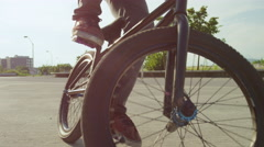SLOW MOTION CLOSE UP: Extreme bmx biker jumping and doing tricks in sunny park Stock Footage