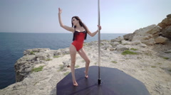 Pole dance workout with portable free standing pole above the sea. Steadicam 4k Stock Footage