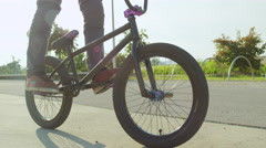 SLOW MOTION CLOSE UP: Young man riding bmx bike in sunny park Stock Footage