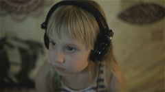 A small girl in headphones watching something on the screen Stock Footage