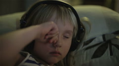 A little girl in headphones rubbing her eyes and yawning Stock Footage