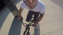 PORTRAIT: Young biker man riding bmx bike and doing tricks in sunny park Stock Footage