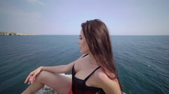 Woman in red monokini swimsuit posing on the edge of rocky cliff above the sea Stock Footage