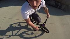 PORTRAIT: Young man riding bmx bike and doing tricks in sunny park Stock Footage