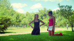 Fit girls talking kneeling on green grass in park Stock Footage
