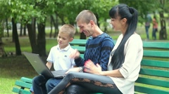 Family of mom dad and son sitting on a bench in the park and looking at a laptop Stock Footage