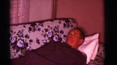 1966: mature man lying on the sofa covered with a gray blanket trying to sleep Arkistovideo