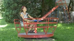 Laughing woman spinning on carousel in playground Stock Footage